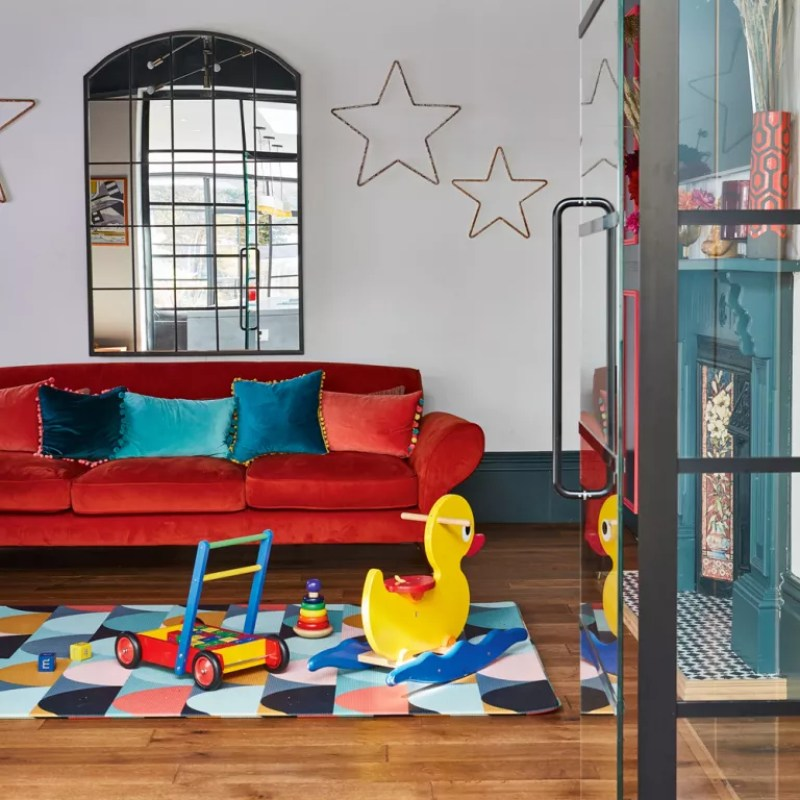 family living room with red sofa and colourful check rug with wooden toys