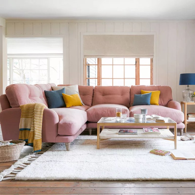 Living room with large pink corner sofa and colourful scatter cushions