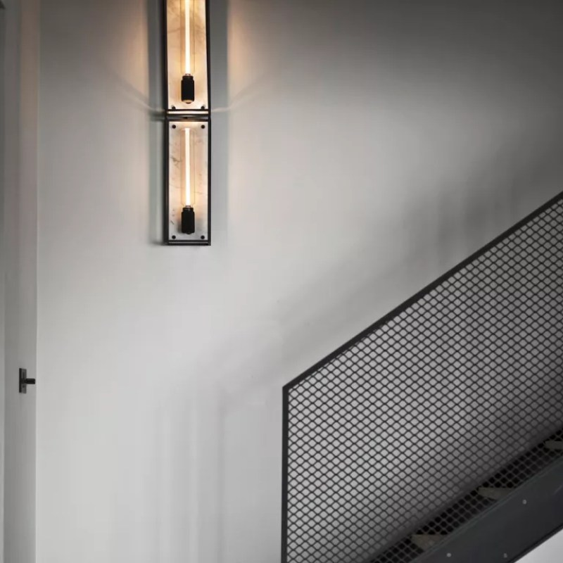 buster and punch wall light on staircase - nest
