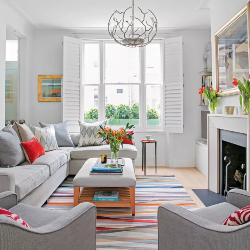 grey living rooom with window shutters colourful rug and grey sofa and armchairs around coffee table