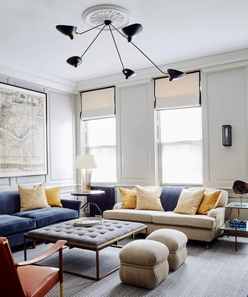 Neutral living room with multiple sofas and large statement ceiling light