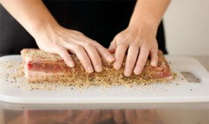 hands rub pork with spice mixture for bacon