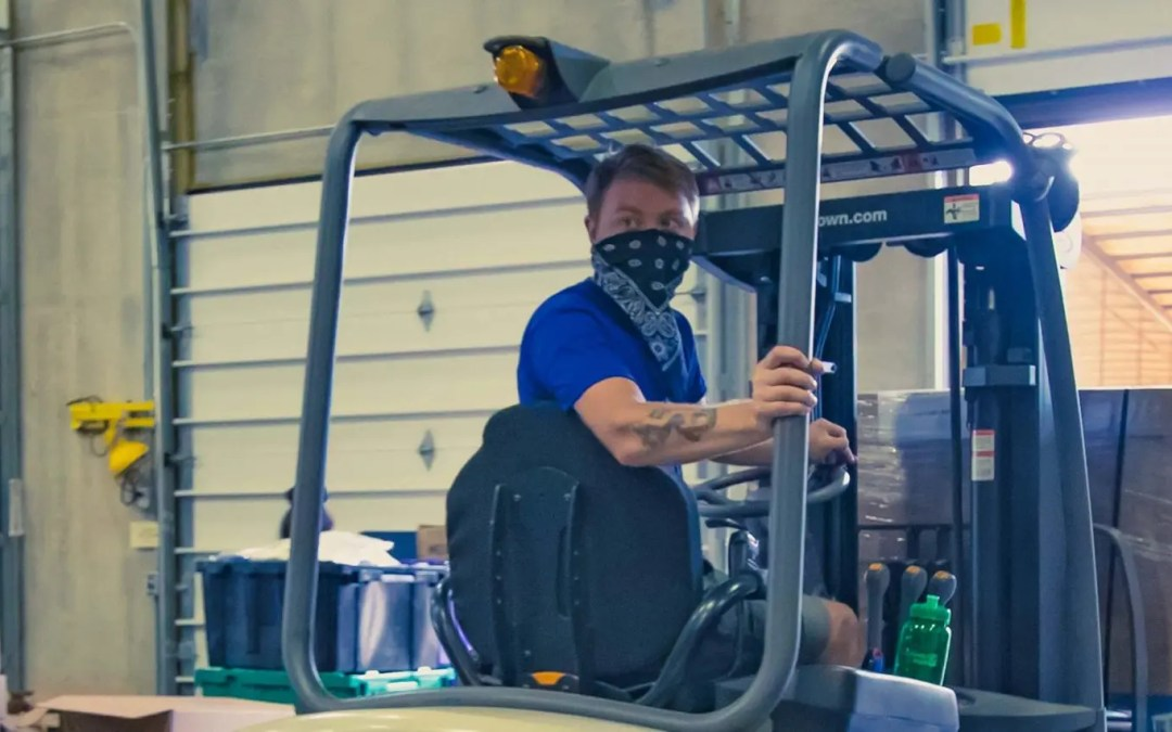 Team member in bandana on a forklift