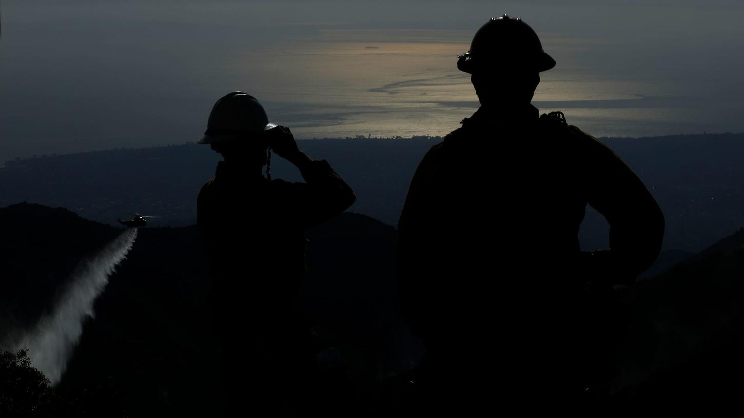 Santa Barbara County firefighters stand on Gibraltar Ridge, located above Santa Barbara and Montecito, as a water drop is made on the Thomas Fire on Dec. 18, 2017. (Credit: Mel Melcon / Los Angeles Times)