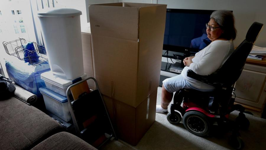 JoAnn Hesson, 68, sits among her moving boxes and personal belongings in her apartment in Rancho Santa Margarita. Hesson took out several high-interest installment loans in 2015 and is considering filing for bankruptcy. She has since moved to Phoenix to be closer to family. (Credit: Mark Boster / Los Angeles Times)