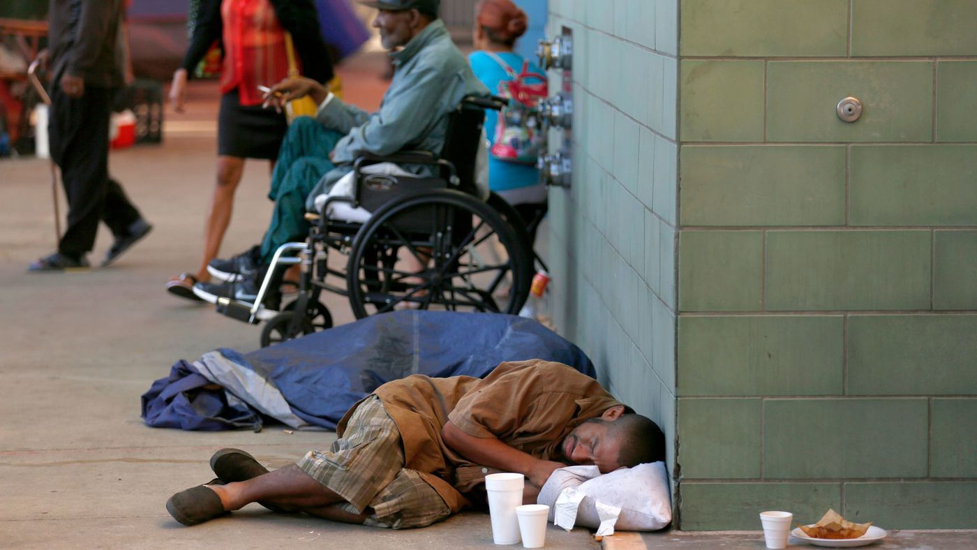 A man sleeps on the sidewalk in front of the Union Rescue Mission on skid row in downtown L.A. in January, 2018. (Credit: Francine Orr / Los Angeles Times)