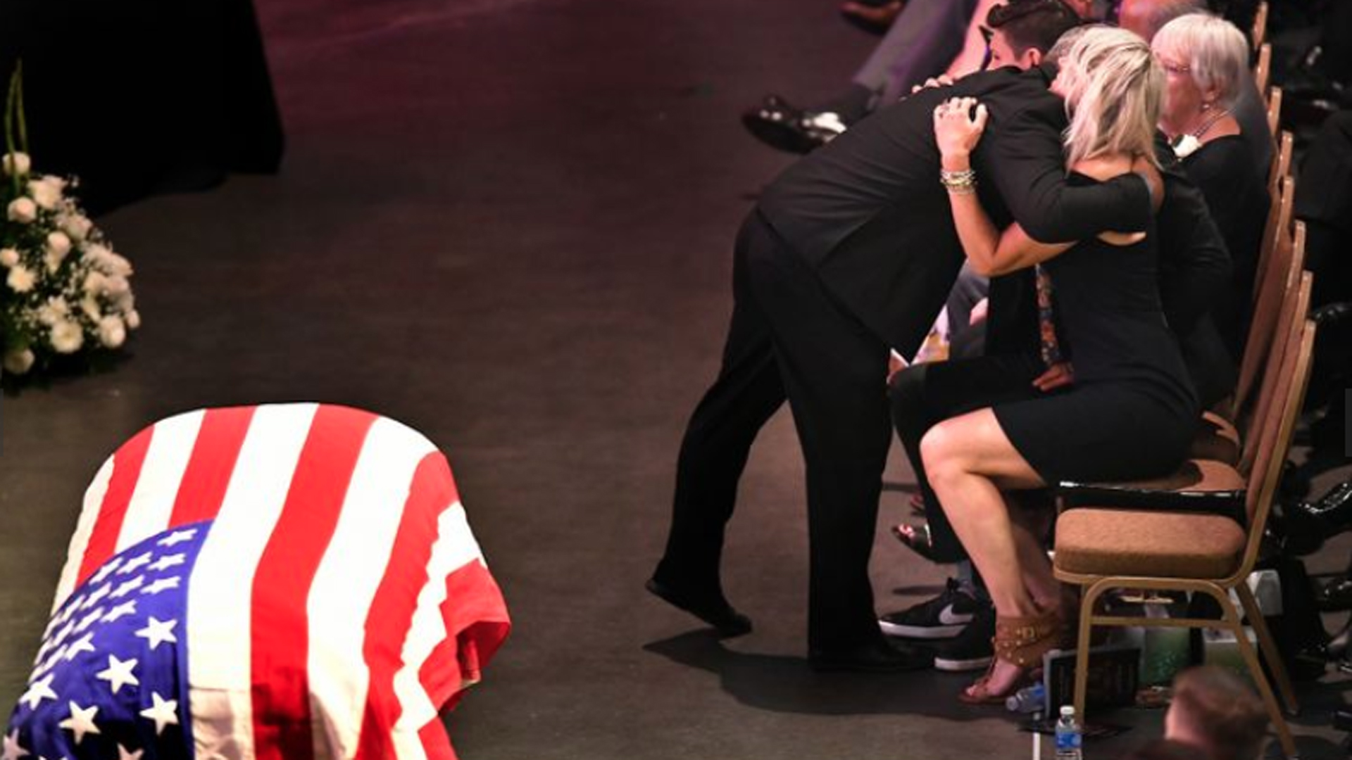 The wife of fallen firefighter Capt. Dave Rosa receives a hug during a memorial service at the Long Beach Convention Center on July 3, 2018. (Credit: Wally Skalij / Los Angeles Times)