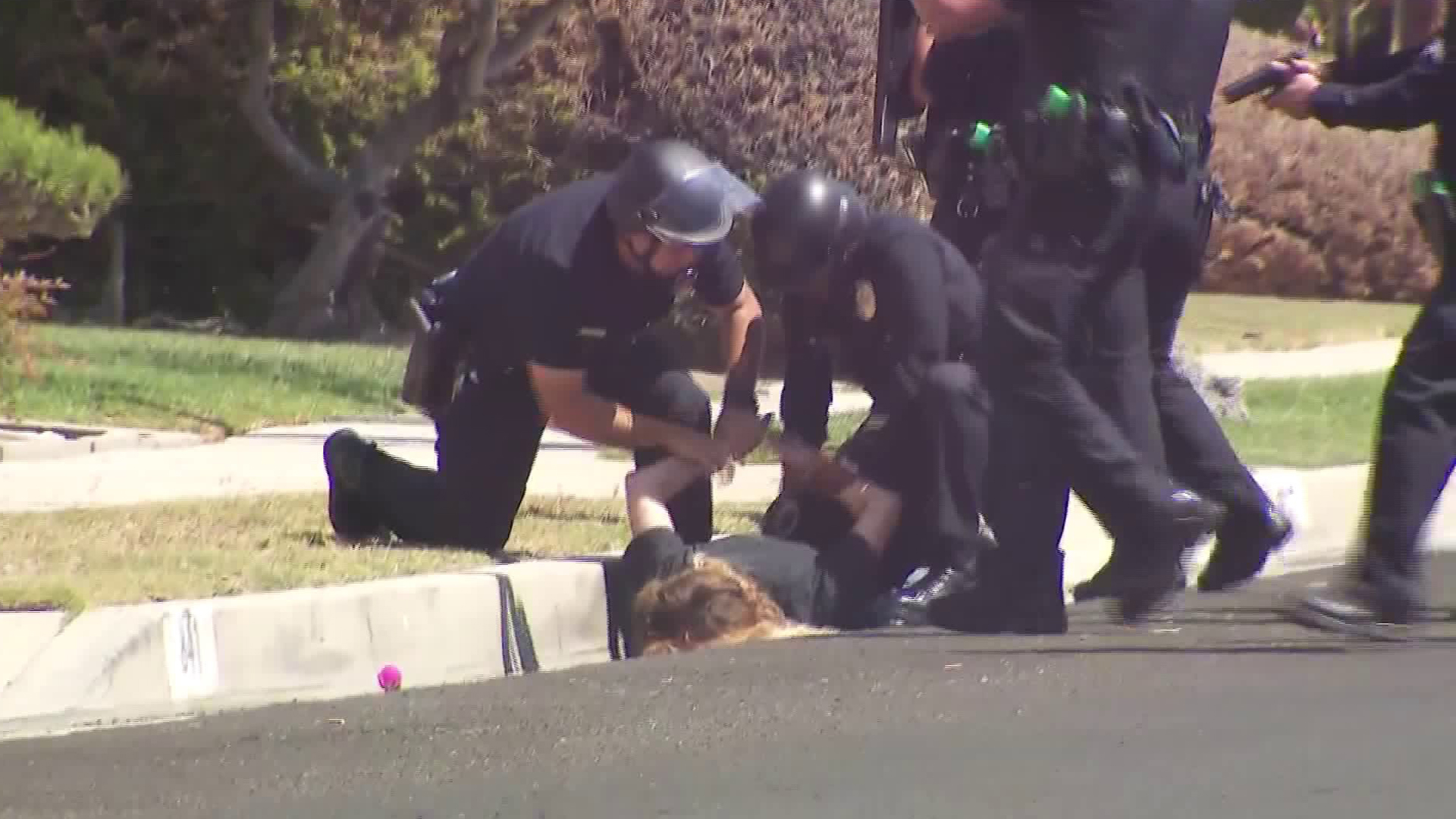 A woman is detained outside a home in the Harbor Gateway neighborhood in connection with a homicide investigation on Sept. 12, 2018. (KTLA)
