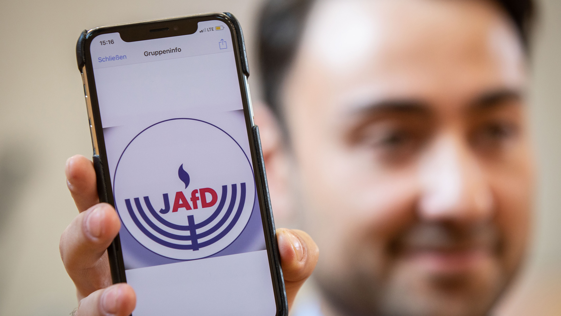 Committee member Leon Hakobian shows on his mobile phone a preliminary draft of a logo for a new Jewish grouping within Germany's far-right AfD party during the group's founding event on Oct. 7, 2018, in Wiesbaden, western Germany. (Credit: FRANK RUMPENHORST/AFP/Getty Images)