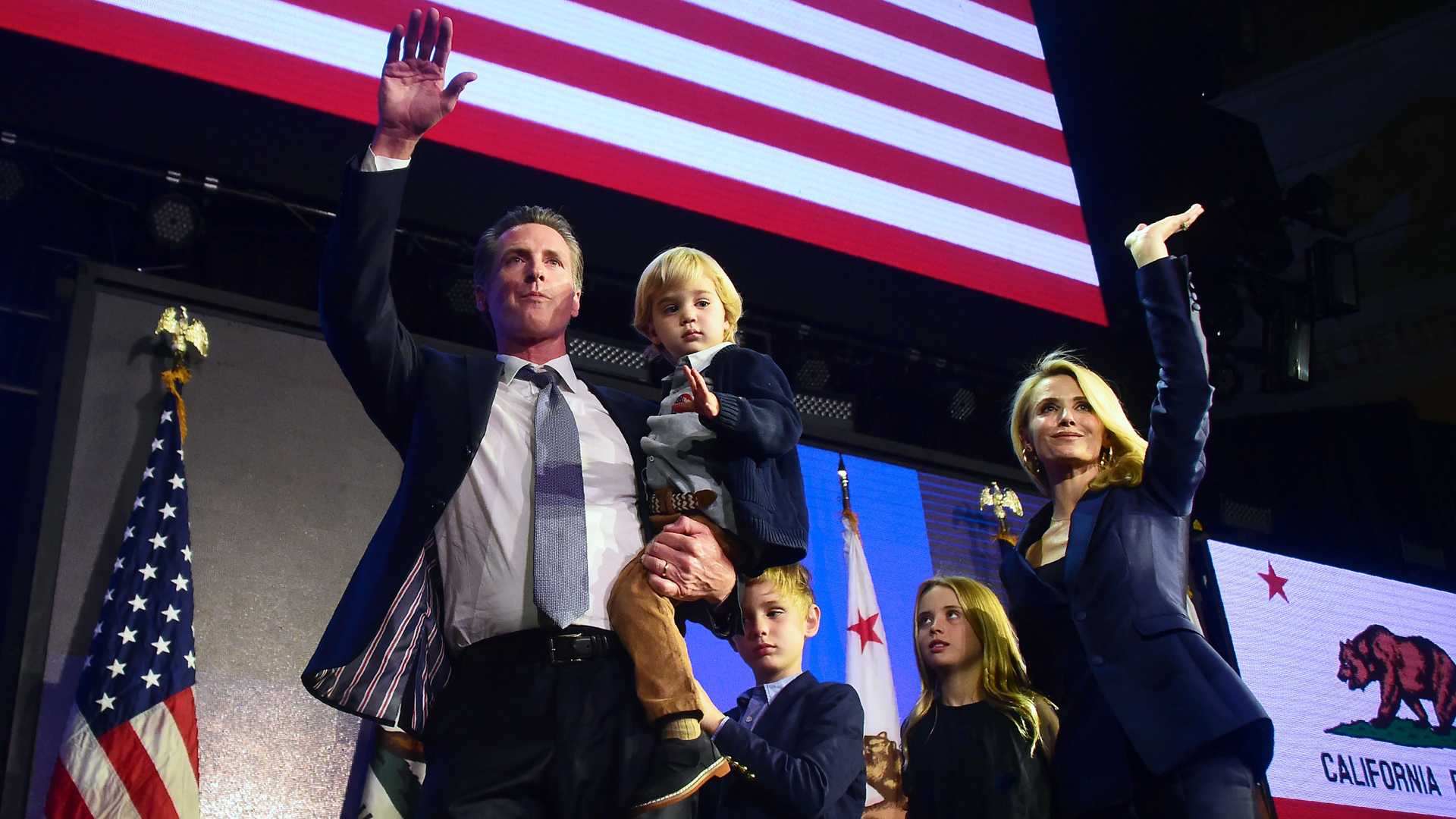 Gov.-elect Gavin Newsom and his family wave to supporters from stage at his election night watch party in Los Angeles on Nov. 6, 2018. (Credit: FREDERIC J. BROWN/AFP/Getty Images)