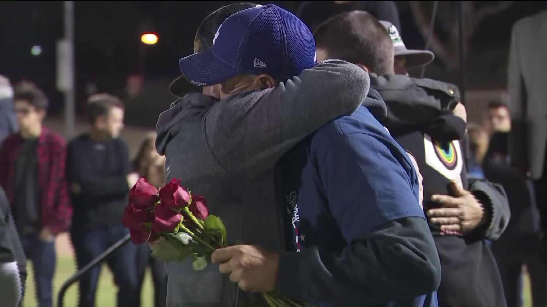 Jason Coffman hands out roses on Nov. 13, 2018, to families during a vigil for the victims of the Thousand Oaks mass shooting. (Credit: KTLA)