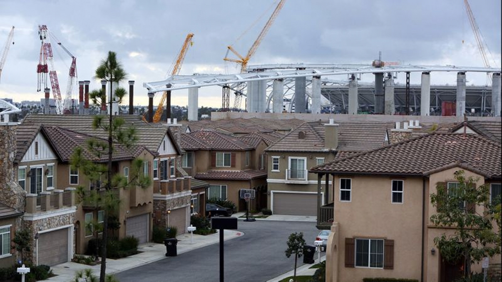 Construction of the Rams-Chargers Complex is seen behind the Renaissance Homes in Inglewood on Feb. 20. (Credit: Dania Maxwell / Los Angeles Times)