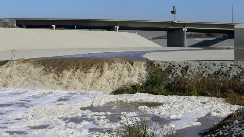 Stormwater flows down the Santa Ana River channel from Prado Dam while hydrologic technicians with the USGS California Water Science Center conduct high-flow velocity and volume measurements. (Credit: Allen J. Schaben / Los Angeles Times)