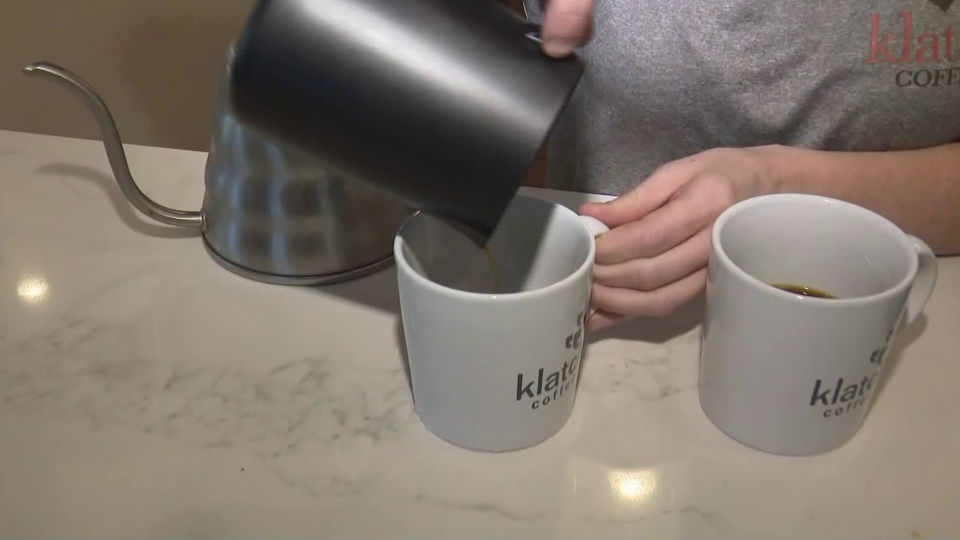A barista pours the world's most expensive coffee into two cups at Klatch Coffee Roaster in San Dimas on May 13, 2019. (Credit: KTLA)