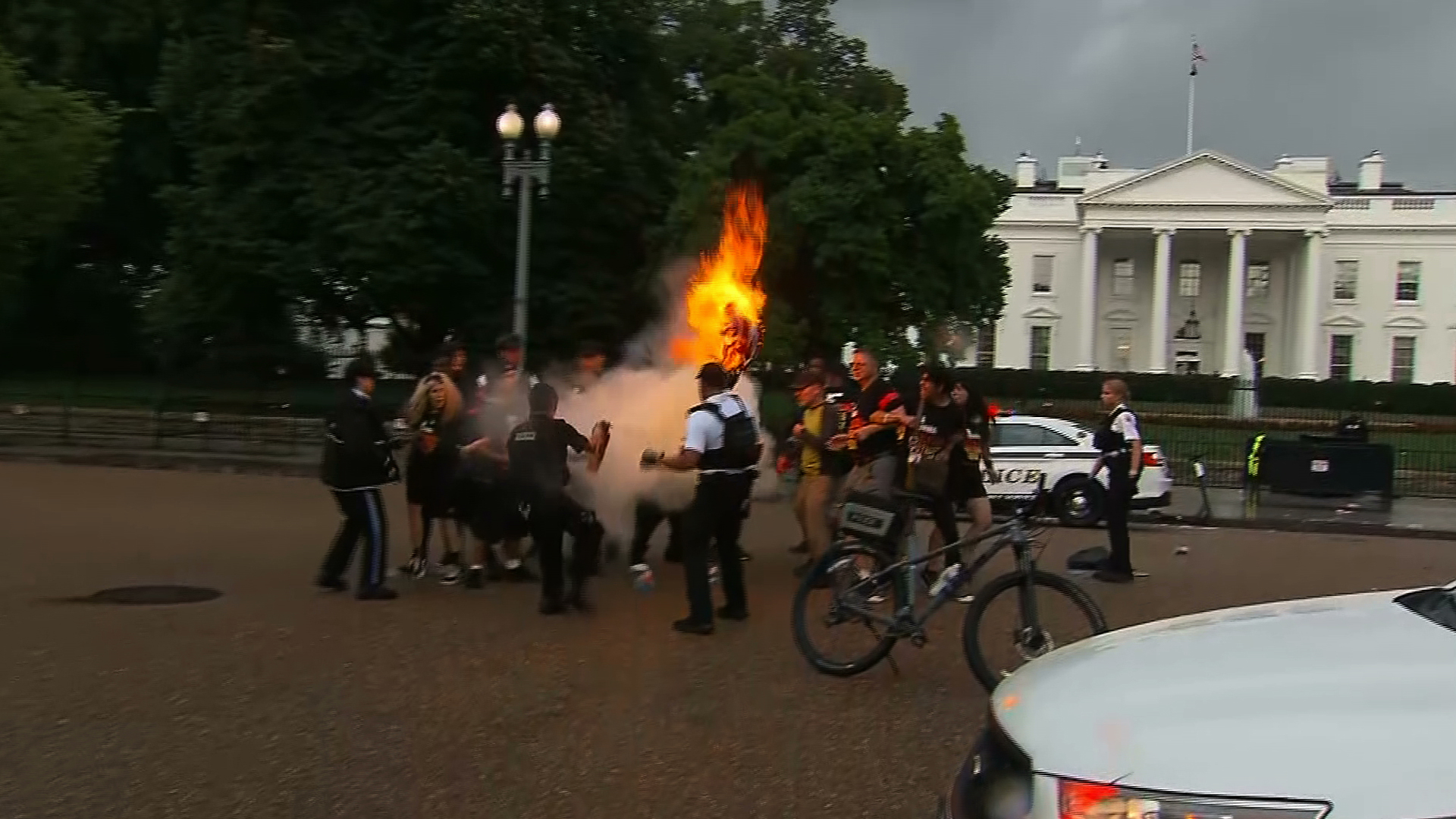 A protest group sets an American flag on fire outside the White House on July 4, 2019. (Credit: CNN)