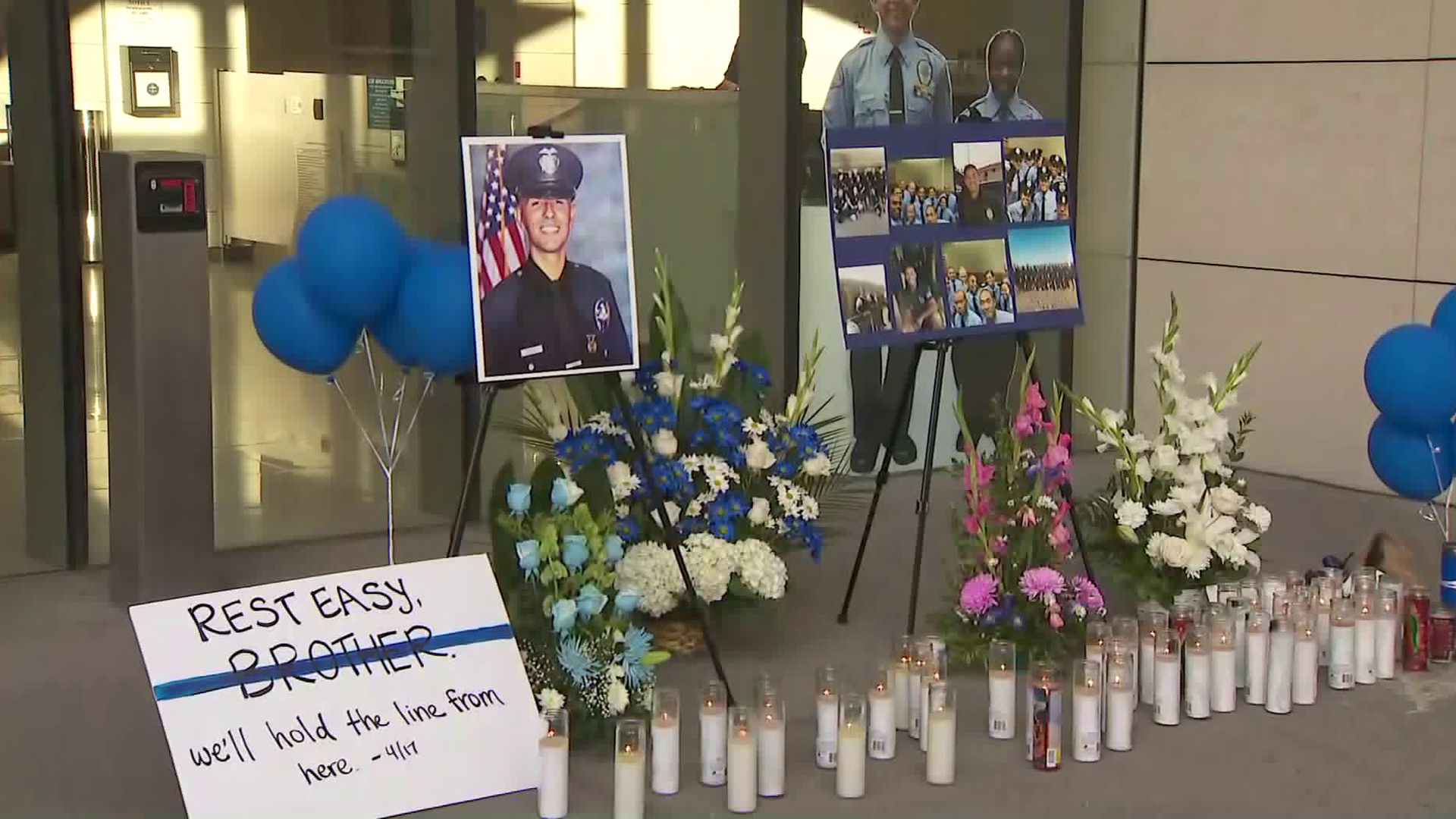 "Candles, photos, balloons, flowers and a sign that reads ""Rest easy brother, we'll hold the line from here,"" appear outside LAPD's headquarters in honor of Officer Juan Diaz on July 28, 2019. (Credit: KTLA)"