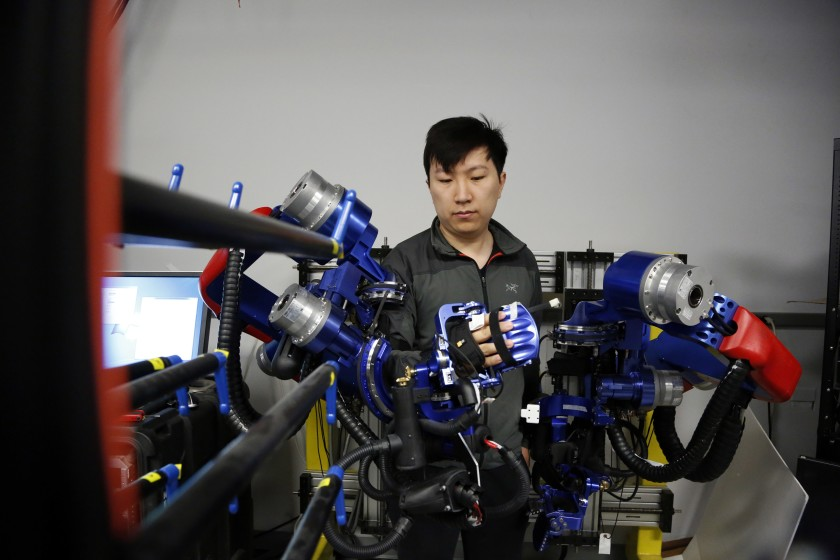 Yang Shen, a Ph.D. candidate in robotics at UCLA, demonstrates how the exoskeleton robot works in this undated photo. (Credit: Katie Falkenberg/Los Angeles Times)