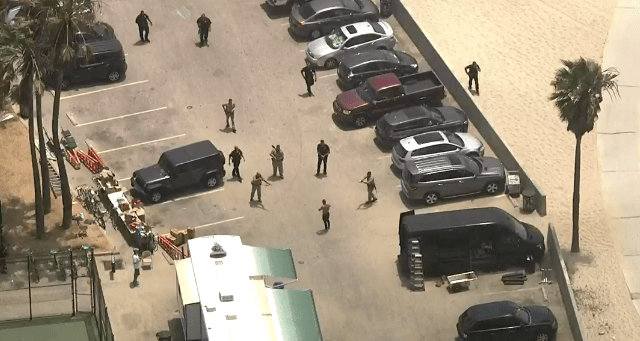Office surround the driver at a Venice Beach Board Walk parking lot following a pursuit on July 12, 2019. (Credit: KTLA)