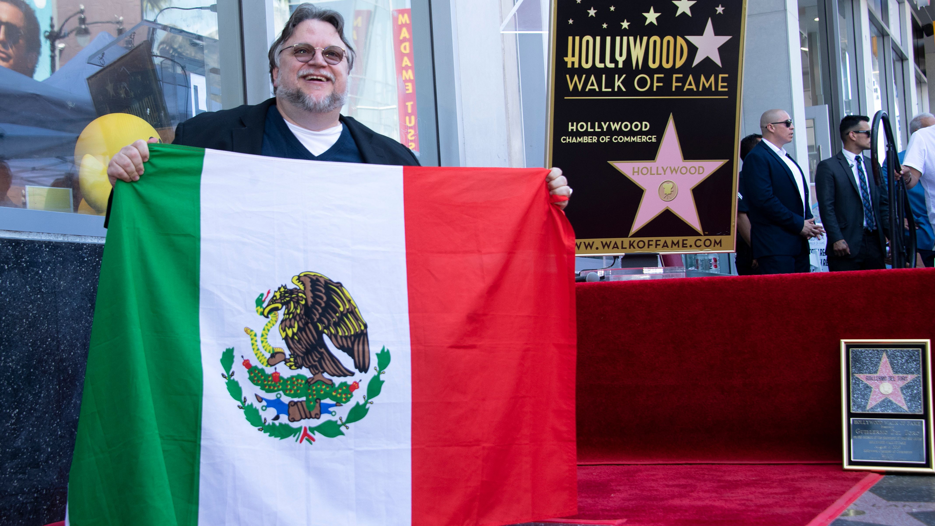 Director Guillermo Del Toro poses with the Mexican flag during the ceremony for his Star on the Hollywood Walk of Fame on Aug. 6, 2019. (Credit: Valerie Macon/AFP/Getty Images)