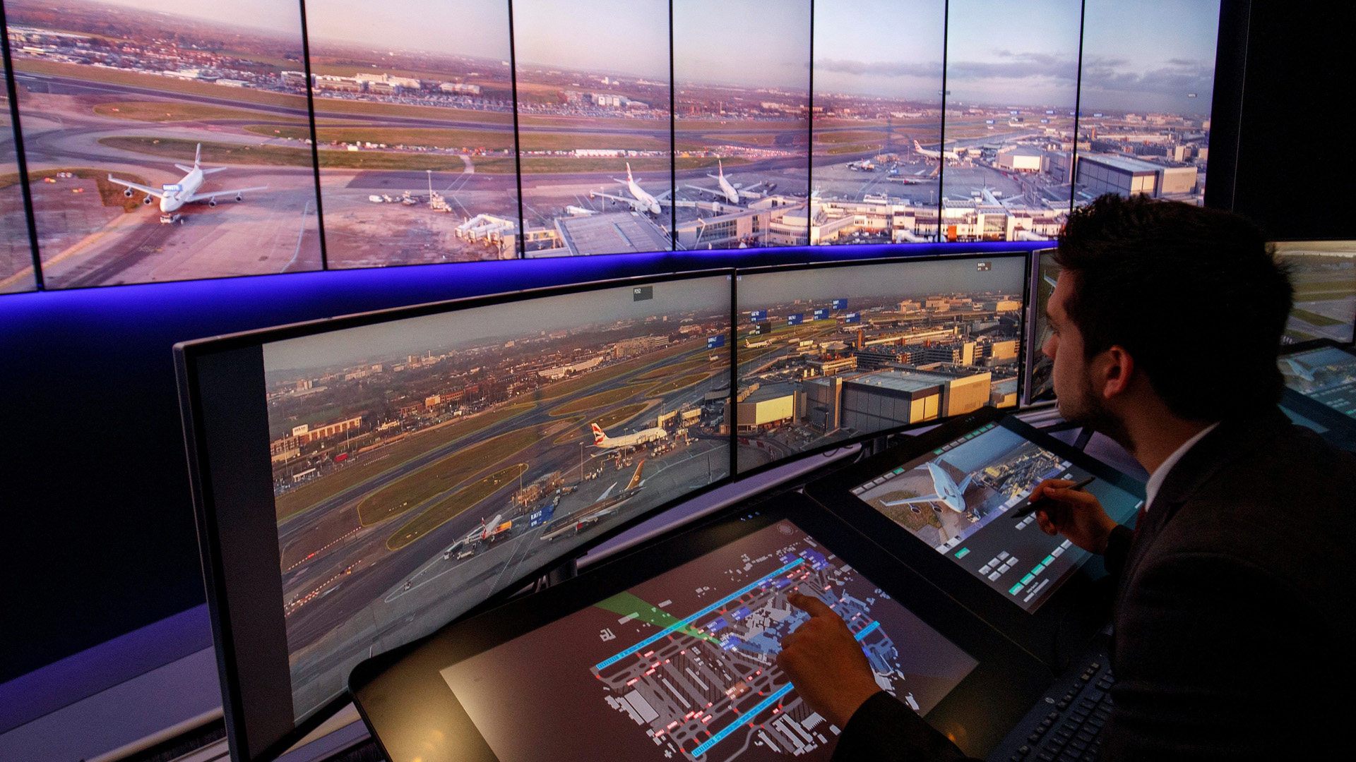 Air traffic control engineers watch screens displaying real-time views of runways and docking gates filmed through cameras combined with artificial intelligence at London Heathrow Airport in west London on Jan. 23, 2019.(Credit: Tolga Akmen/AFP/Getty Images)