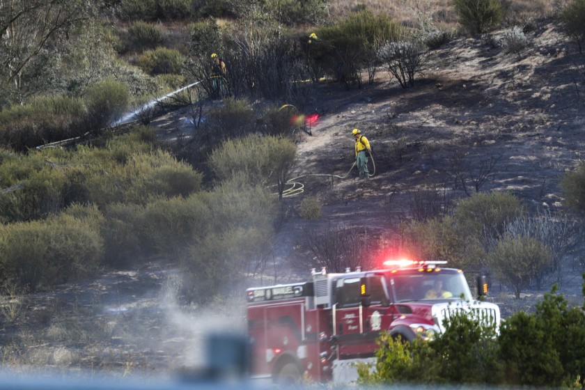 Firefighters put out a hot spot while battling the Old Water Fire in San Bernardino on Oct. 24, 2019. (Credit: Irfan Khan/Los Angeles Times)