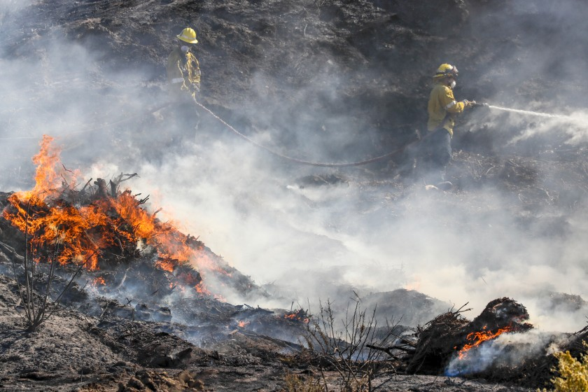 Firefighters battle the Tick fire along Sierra Highway in Santa Clarita on Oct. 25, 2019. (Credit: Irfan Khan/Los Angeles Times)