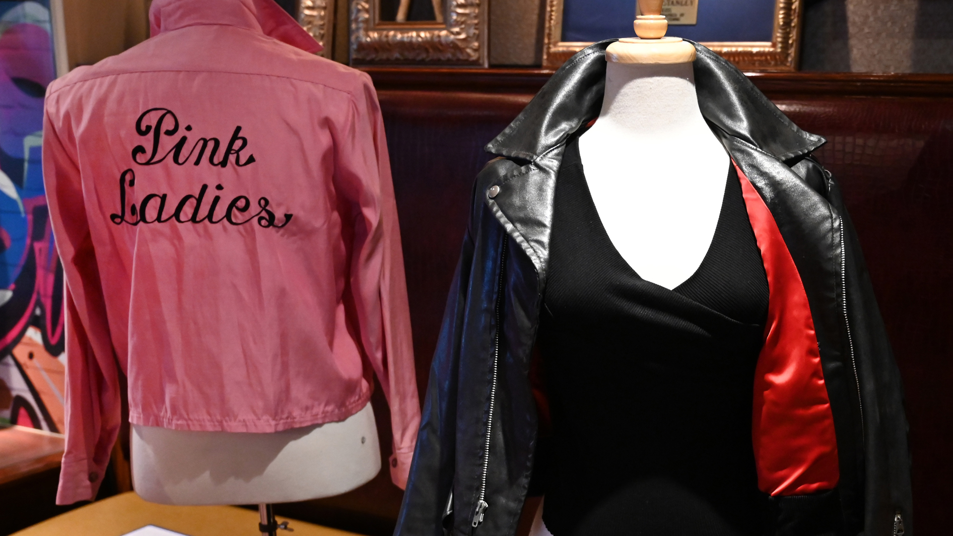 """Olivia Newton-John's famous black leather jacket worn in the blockbuster film """"Grease"""" and her Grease """"Pink Ladies"""" jacket worn in the film are shown during a Julien's Auctions press preview at Hard Rock Cafe in New York on October 16, 2019.(Credit: Timothy A. Clary/AFP via Getty Images)"""