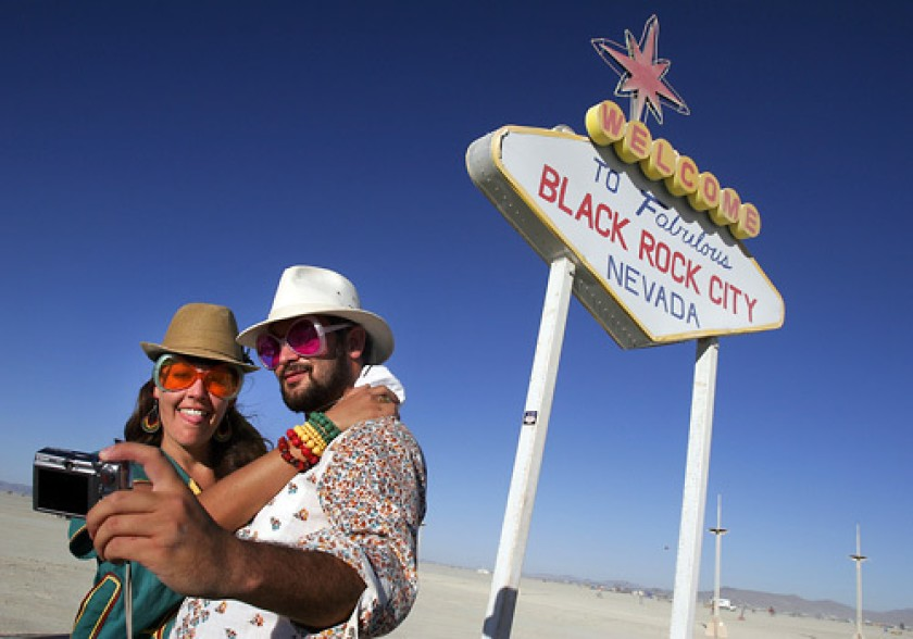 Simone Oliver of San Diego and Eric Weisz of San Francisco take a picture in front of a welcome to Black Rock City sign during the Burning Man festival in 2008. (Credit: Spencer Weiner / Los Angeles Times)