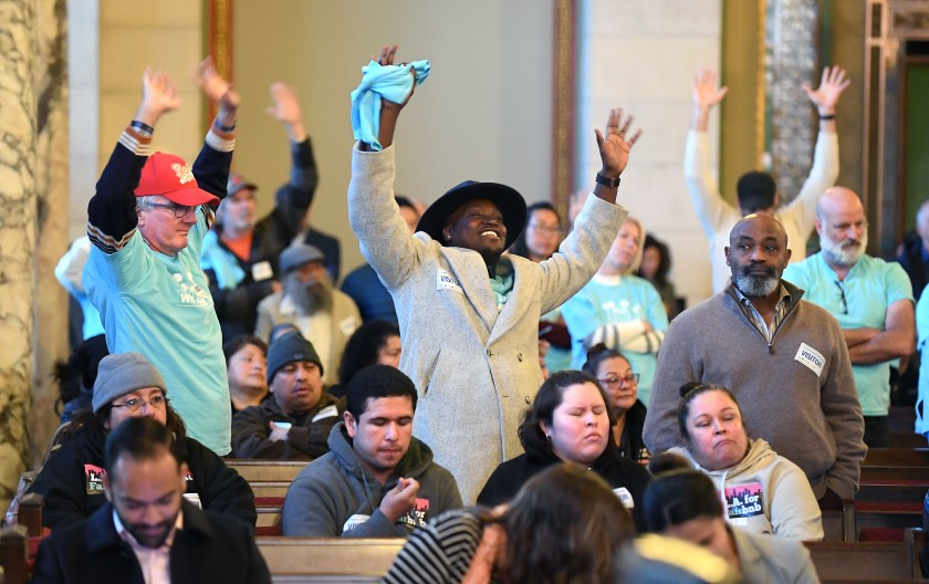 People who support legalizing and regulating short-term rentals of second homes wave their hands in agreement with a speaker during a Planning Commission meeting at Los Angeles City Hall on Dec. 19, 2019. (Credit: Wally Skalij / Los Angeles Times)
