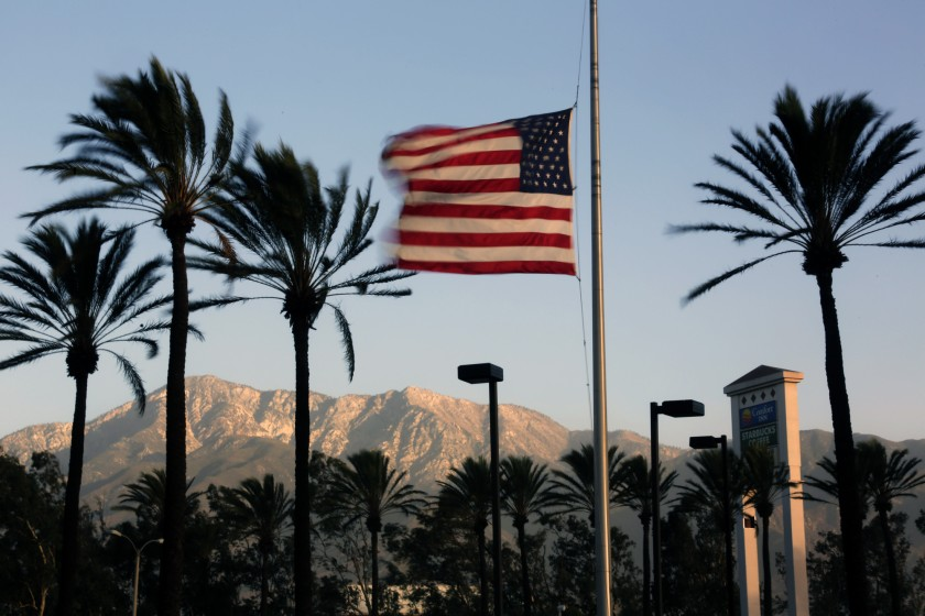 Winds whip palm trees and a U.S. flag in this undated photo. (Credit: Irfan Khan / Los Angeles Times)