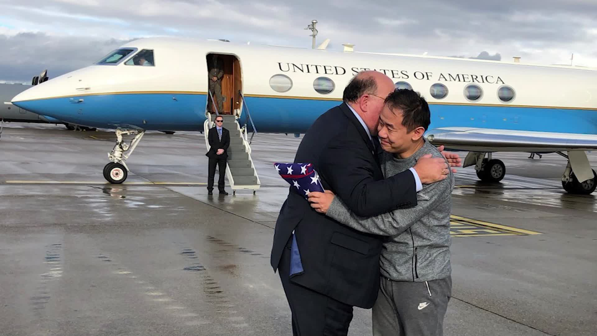 Chinese-American graduate student Xiyue Wang, detained for years on suspicion of being a spy, hugs an official after being freed from Iran on Dec. 7, 2019. (Credit: CNN)