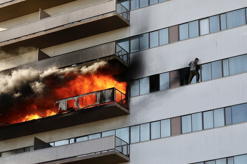 A man clings to the side of Barrington Plaza on Jan. 29, 2020, as flames engulf an apartment balcony. (Credit: Al Seib/Los Angeles Times)