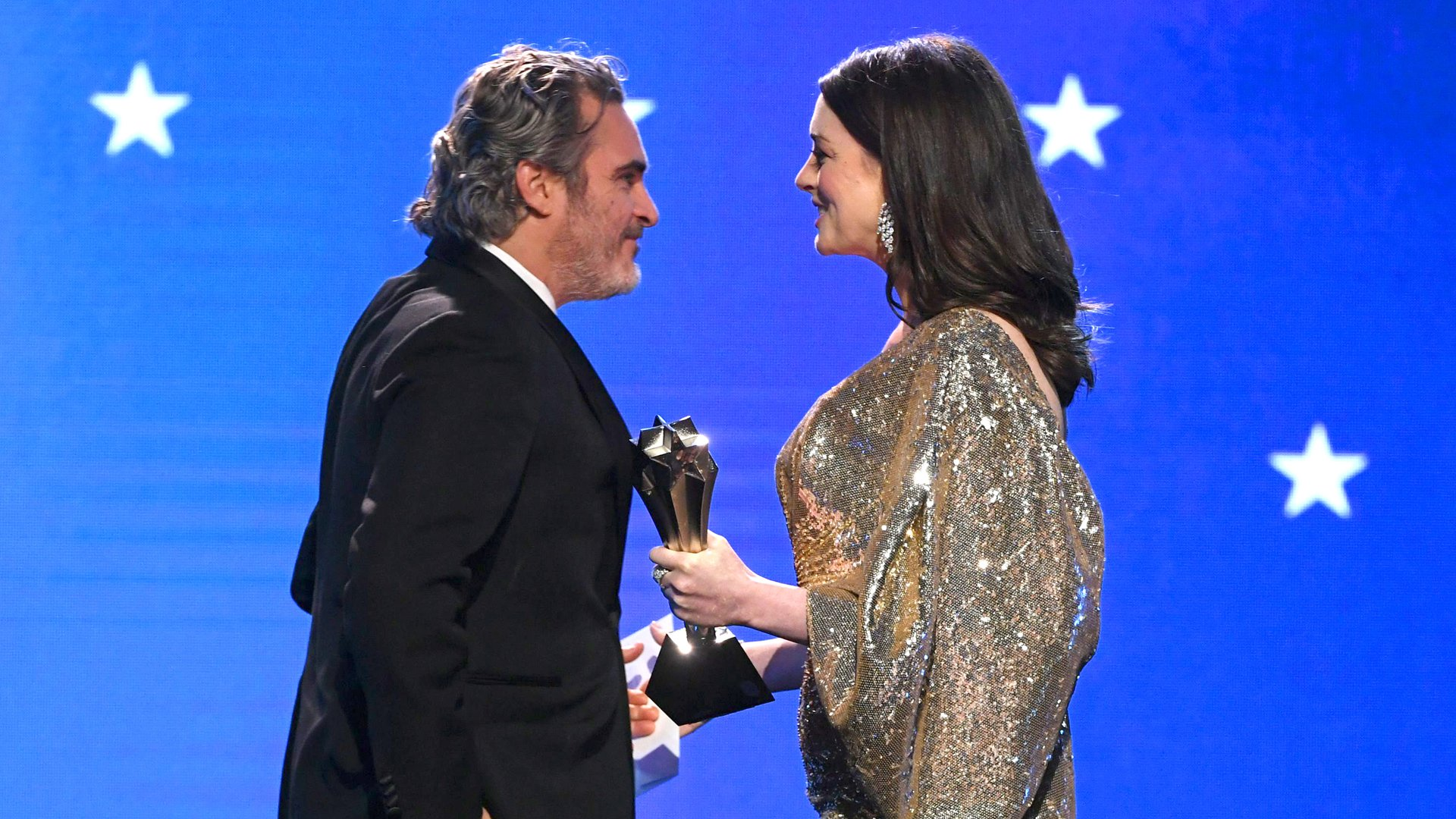 Joaquin Phoenix accepts the Best Actor award for 'Joker' from Anne Hathaway onstage during the 25th Annual Critics' Choice Awards at Barker Hangar on January 12, 2020 in Santa Monica, California. (Credit: Kevin Winter/Getty Images for Critics Choice Association)