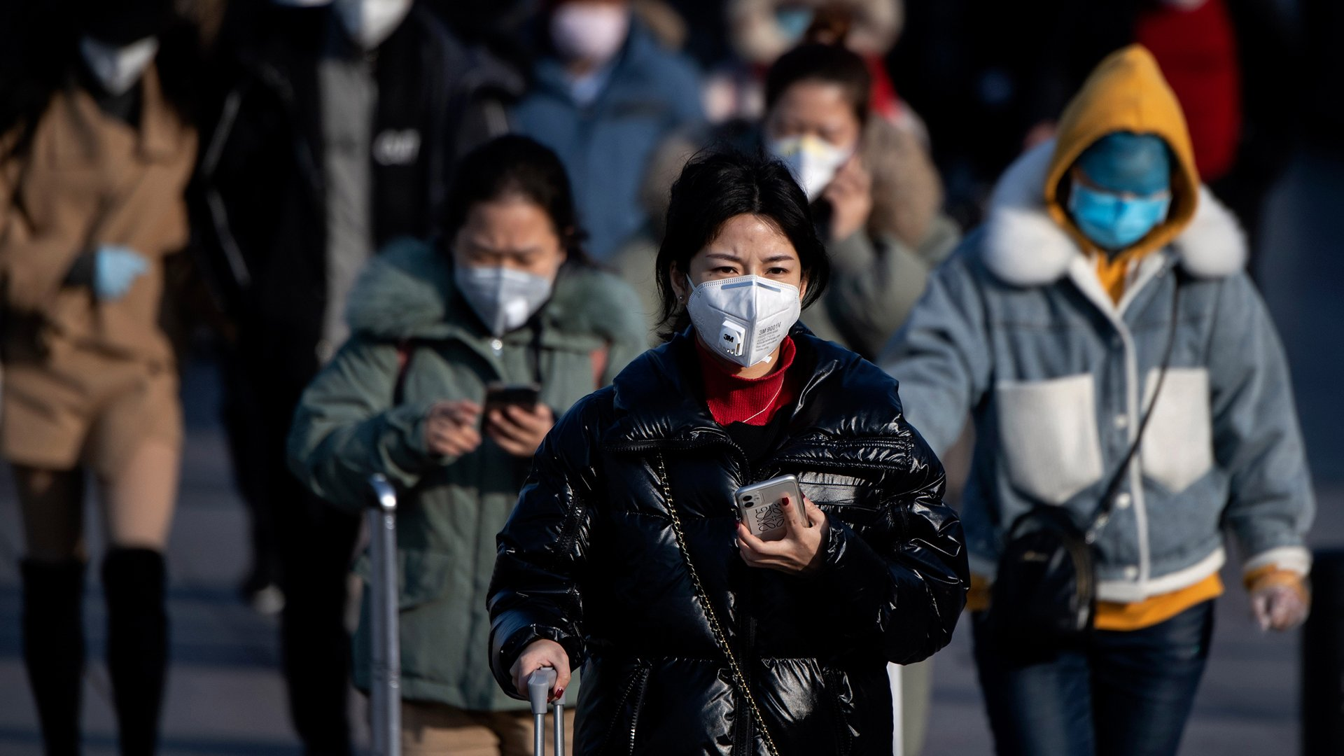 Travelers wearing face masks arrive from various provinces at the Beijing Railway Station on February 3, 2020. (Credit: Noel Celis/AFP/Getty Images)