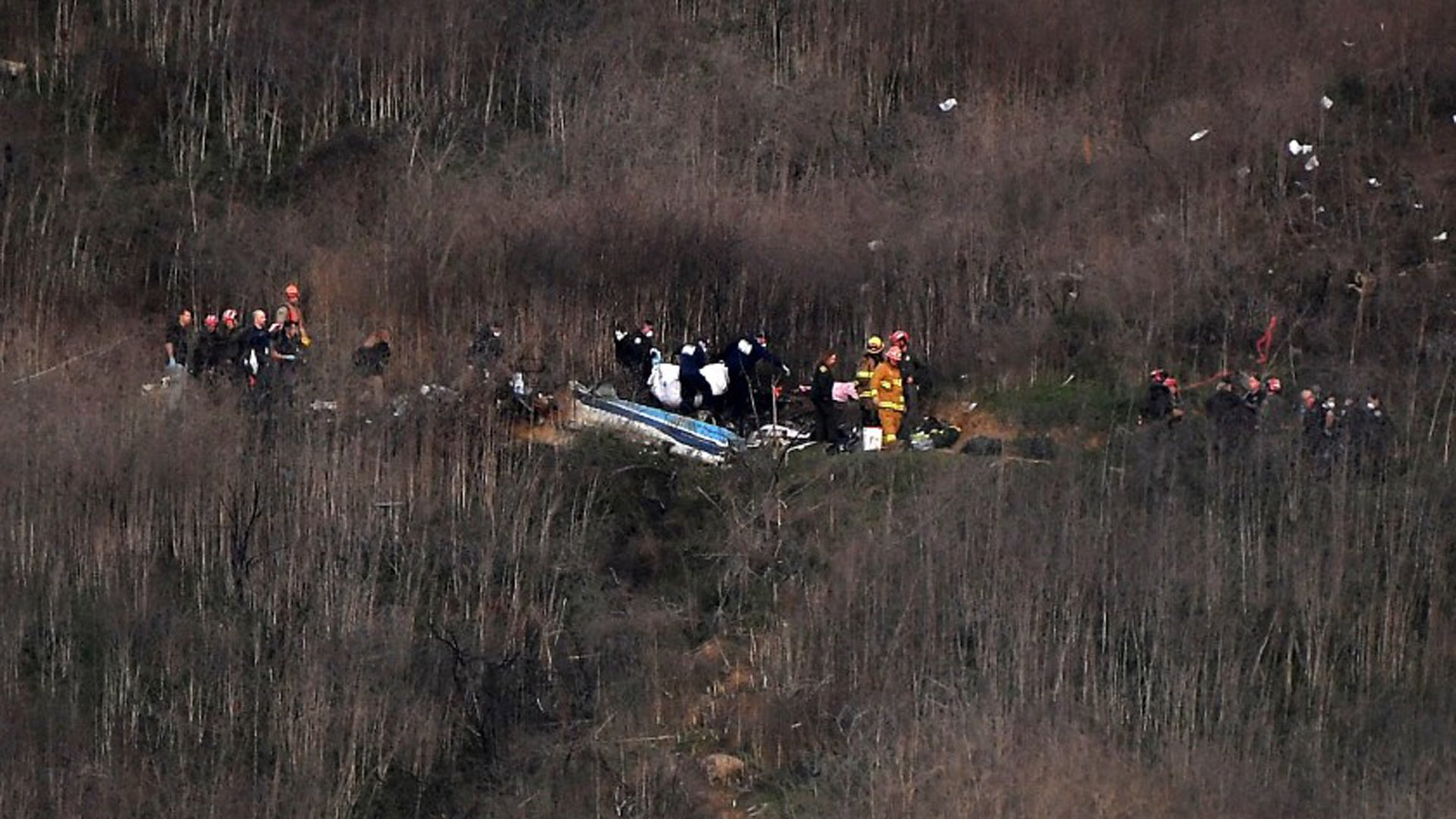 Officials remove a body from the wreckage in Calabasas where Kobe Bryant and his daughter Gianna were among nine dead in a helicopter crash. (Credit: Christina House / Los Angeles Times)