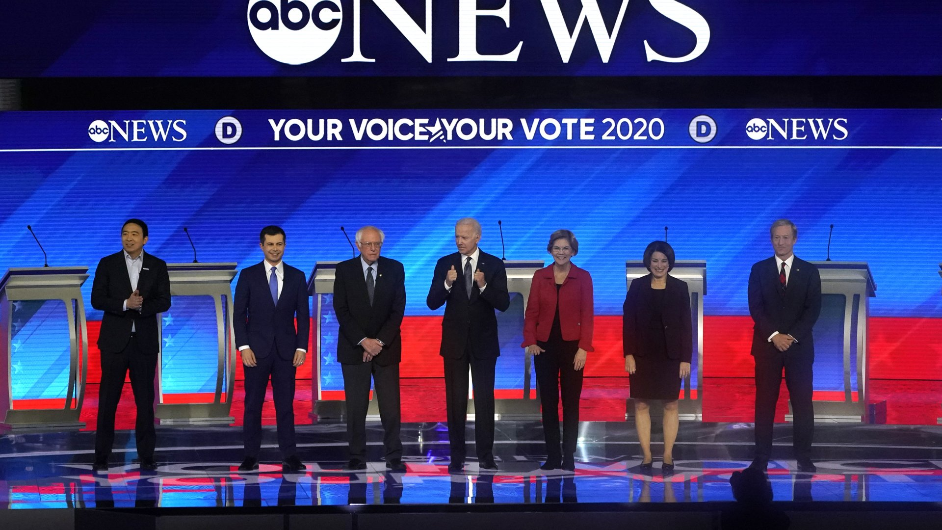 From left: Democratic presidential hopefuls Andrew Yang, Pete Buttigieg, Sen. Bernie Sanders, former Vice President Joe Biden, Sen. Elizabeth Warren, Sen. Amy Klobuchar and Tom Steyer arrive onstage for the eighth Democratic primary debate of the 2020 presidential campaign season at St. Anselm College in Manchester, New Hampshire, on Feb. 7, 2020. (Credit: Timothy A. Clary / AFP / Getty Images)