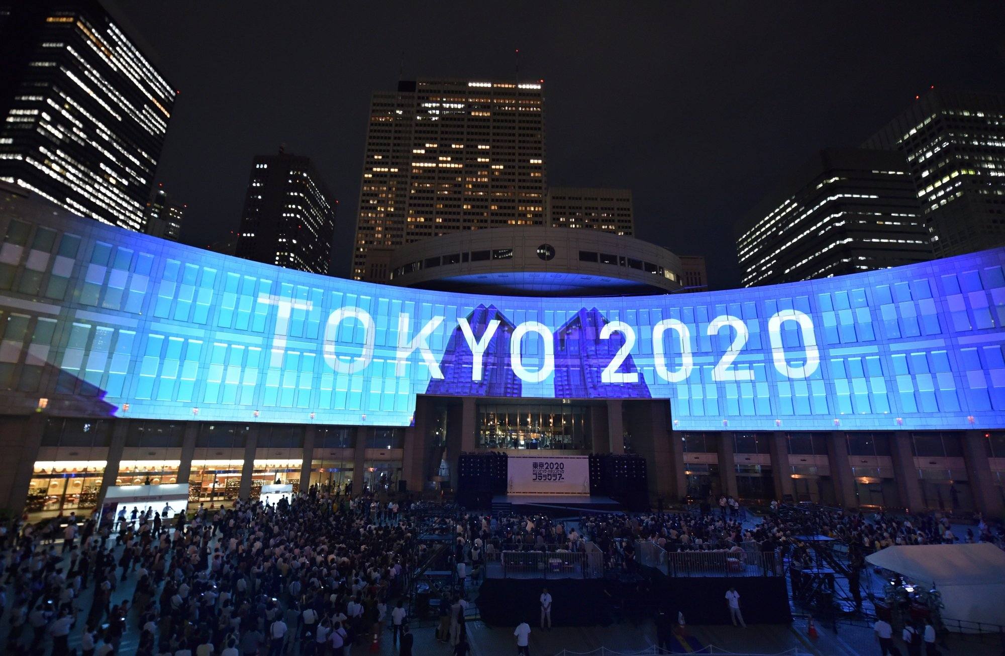 """A projection that reads """"Tokyo 2020"""" is seen during a ceremony marking three years to go before the start of the Tokyo 2020 Olympic games at the Tokyo Metropolitan Assembly Building on July 24, 2017. (Credit: KAZUHIRO NOGI/AFP via Getty Images)"""