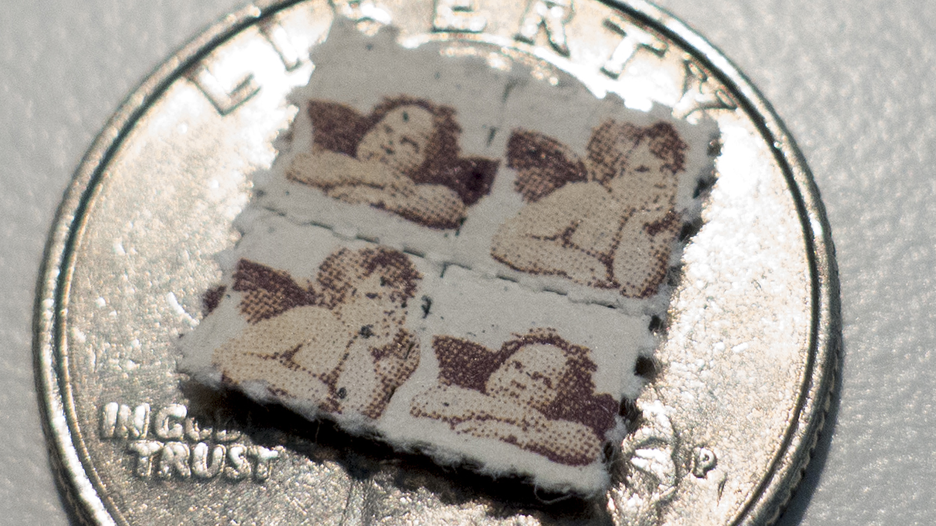 This photo shows LSD tabs on top of a U.S. quarter on April 12, 2017, in Washington, DC. (Credit: Paul J. Richards / AFP / Getty Images)