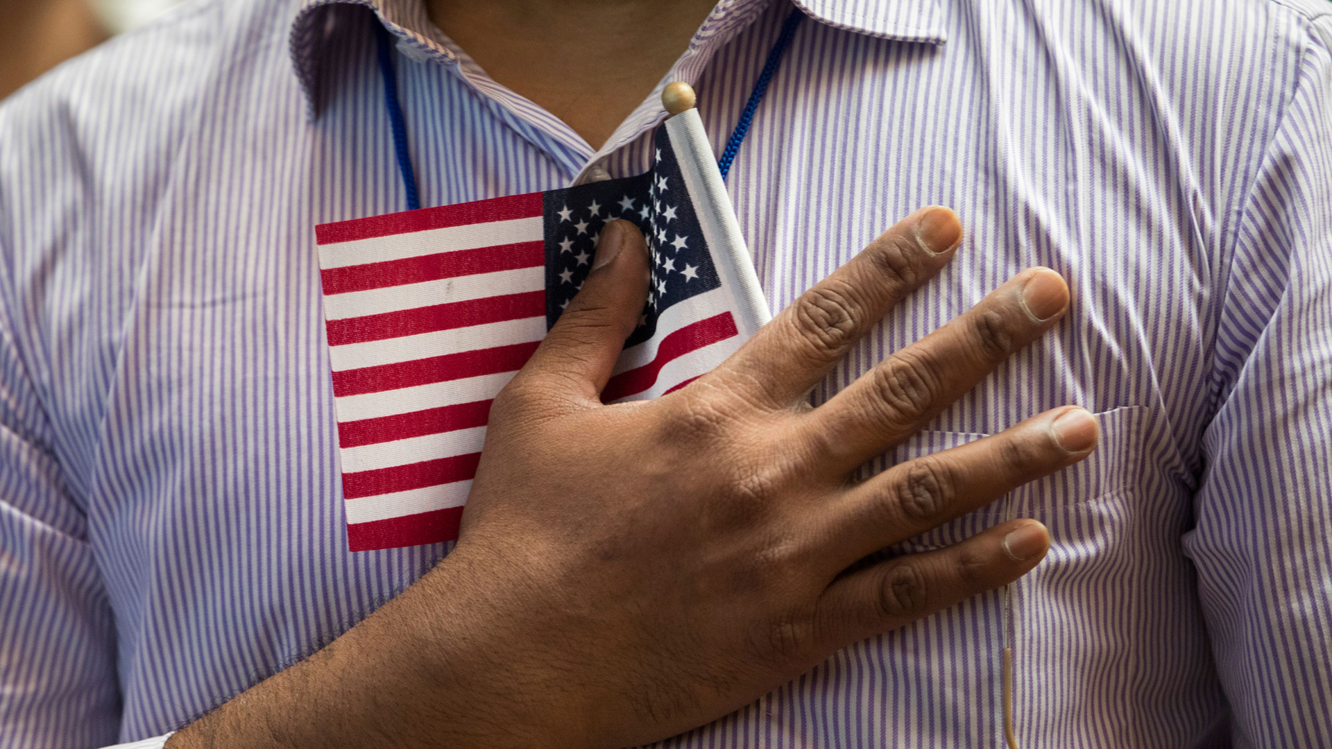 A new U.S. citizen holds a flag to his chest during the Pledge of Allegiance during a naturalization ceremony at the New York Public Library, July 3, 2018, in New York City. (Drew Angerer/Getty Images)