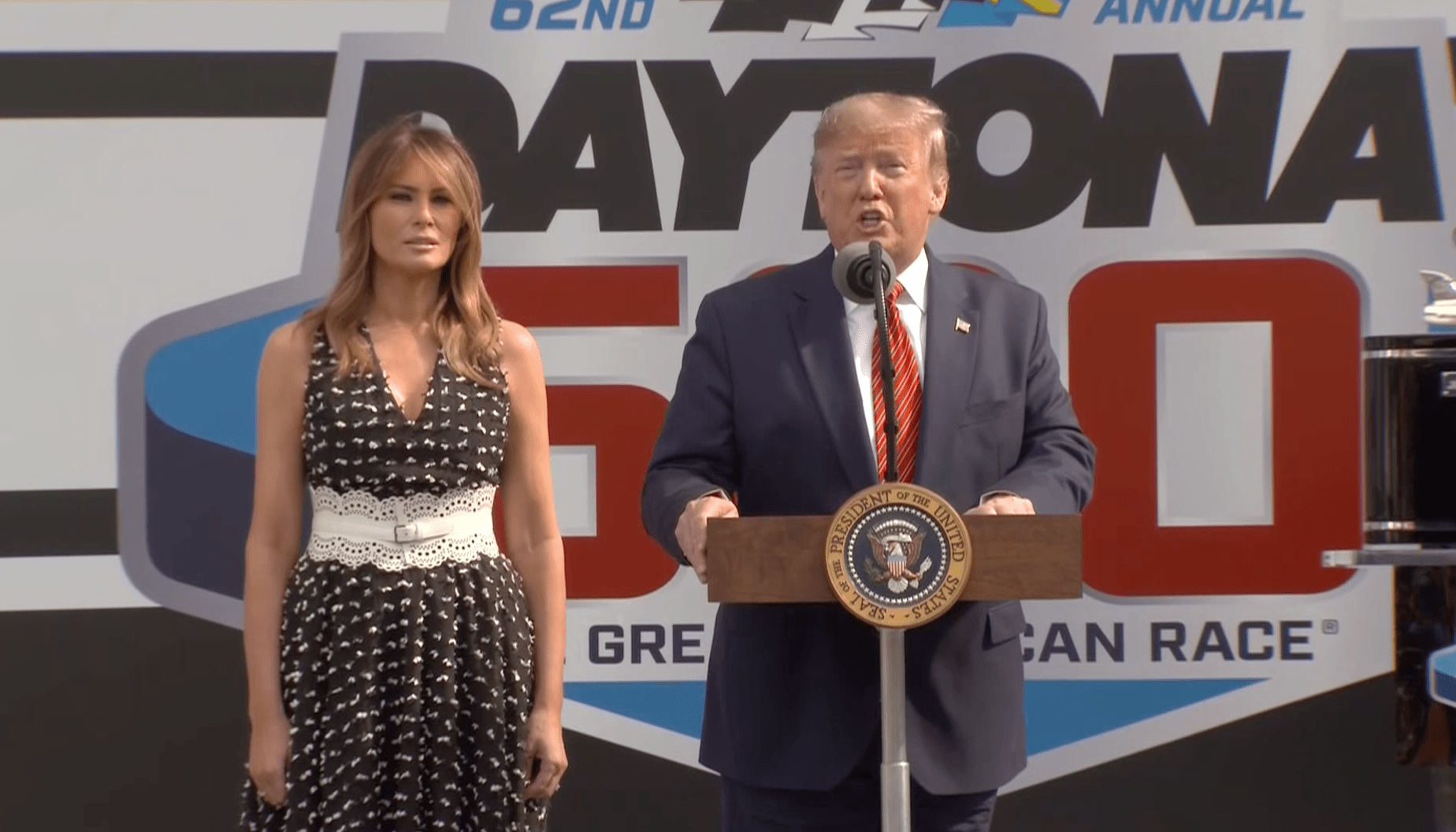Donald Trump, standing beside Melania Trump, addresses the crowd at Daytona 500 in Florida on Feb. 16, 2020. (Credit: CNN)