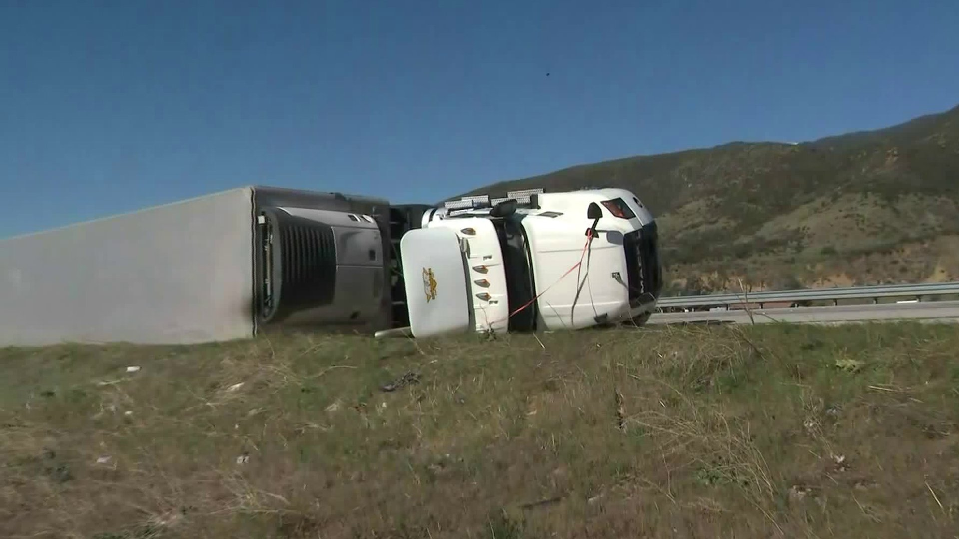 A semitruck came to rest on its side after being knocked over by high winds on the 15 Freeway in Fontana on Feb. 11, 2020. (Credit: KTLA)