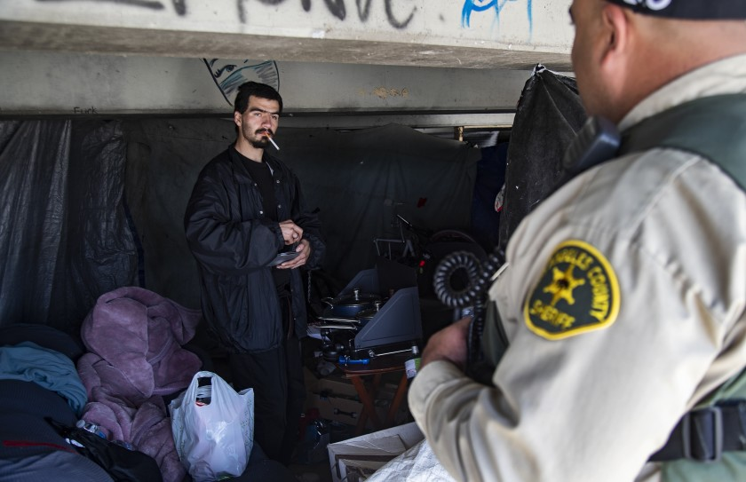 L.A. County Sheriff Deputy Michael Tadrous talks with Shawn Troncozo, 24, about how to prevent becoming infected with the novel coronavirus during an outreach effort in El Monte in March, 2020. (Gina Ferazzi/Los Angeles Times)