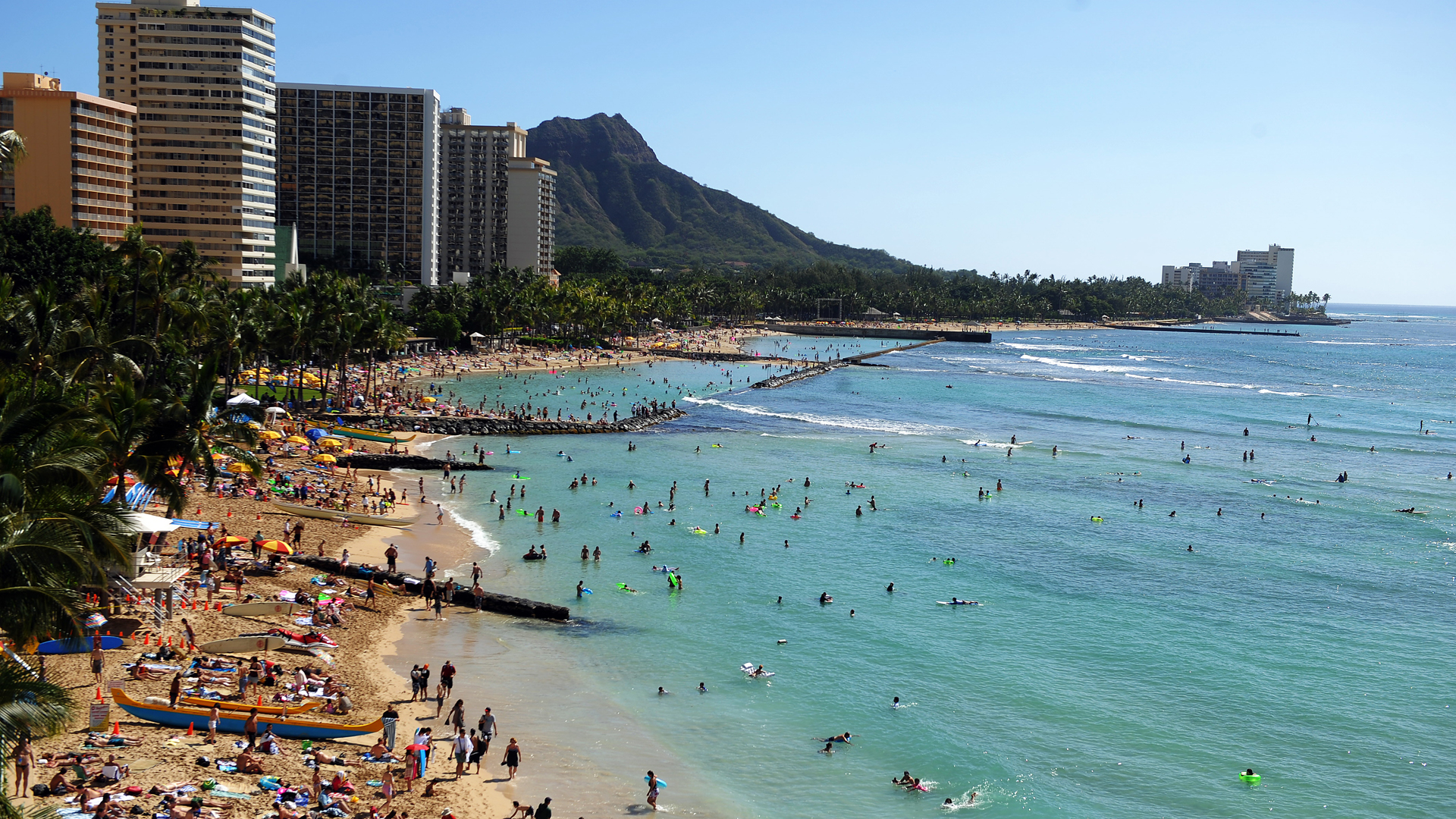 Tourists enjoy sunbathing, surfing, boating and swimming at Waikiki beach in Honolulu, Hawaii, on Jan. 1, 2010. (JEWEL SAMAD/AFP via Getty Images)