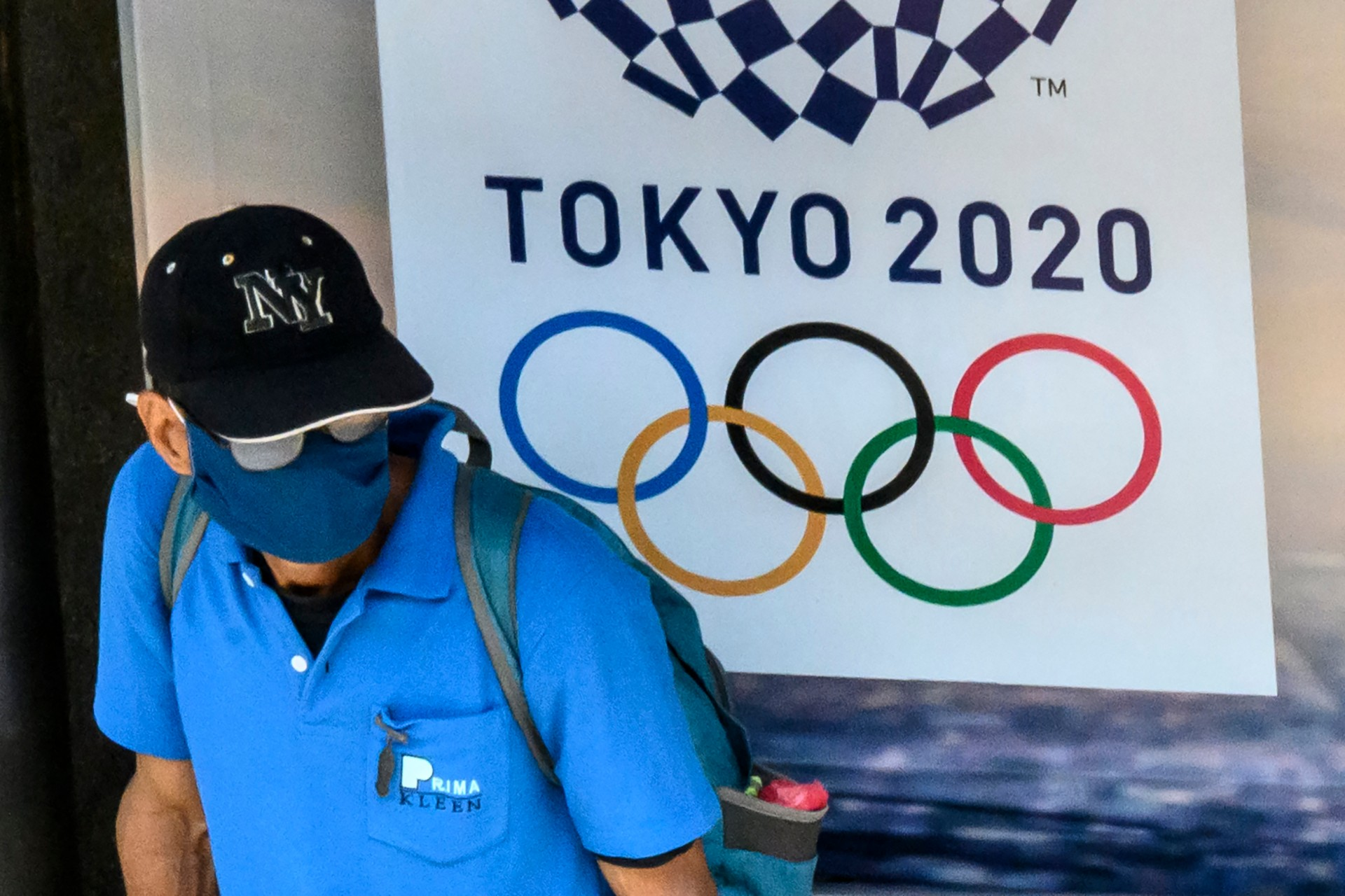 A man, wearing a face mask as a preventive measure against the spread of the COVID-19 novel coronavirus, sits at a bus stop in front of an advertisement for the Tokyo 2020 Summer Olympics Games in Bangkok on March 23, 2020. (MLADEN ANTONOV/AFP via Getty Images)
