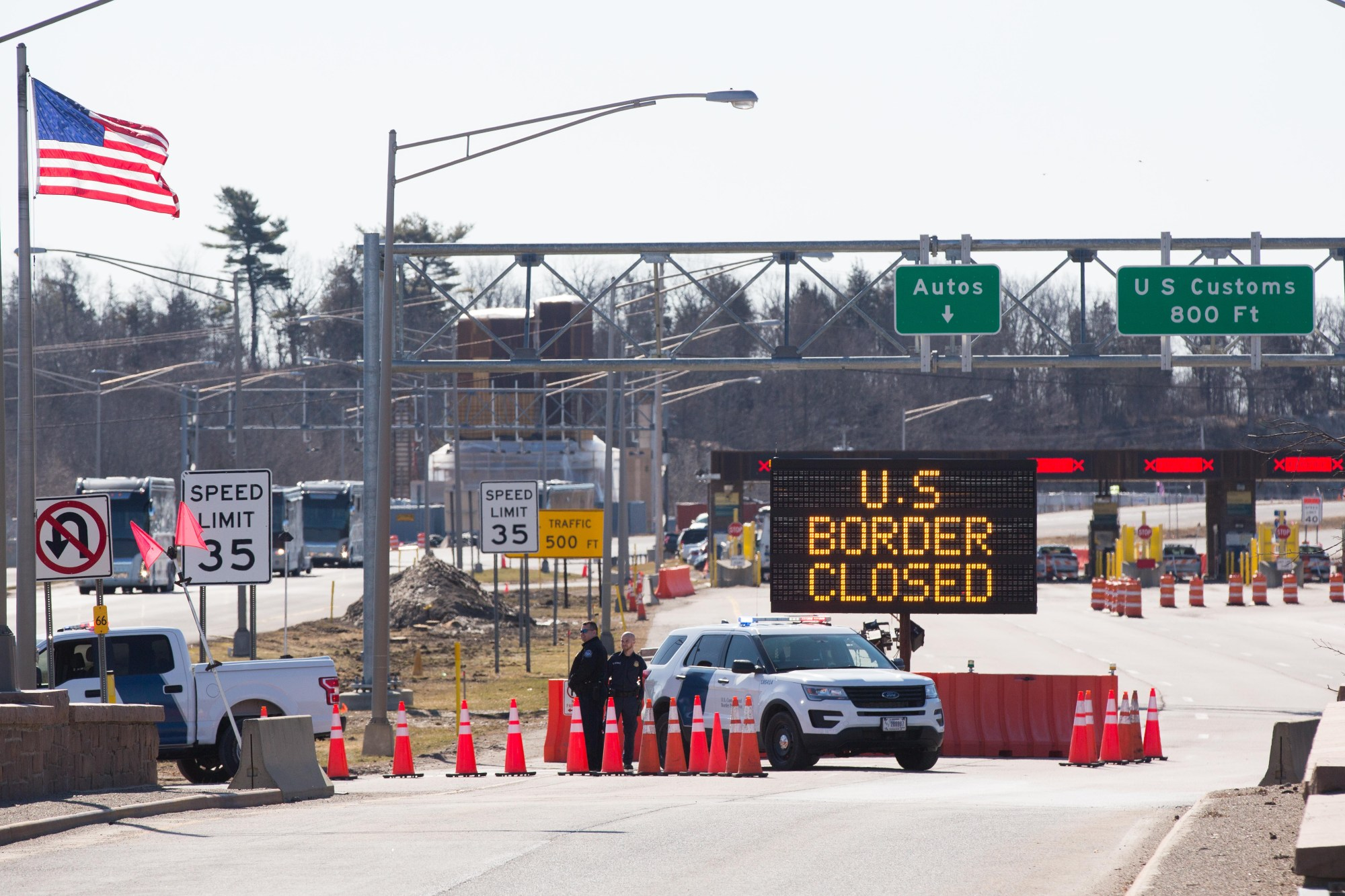 U.S. Customs officers stand beside a sign saying that the U.S. border is closed at the U.S.-Canada border in Lansdowne, Ontario, on March 22, 2020. (LARS HAGBERG/AFP via Getty Images)