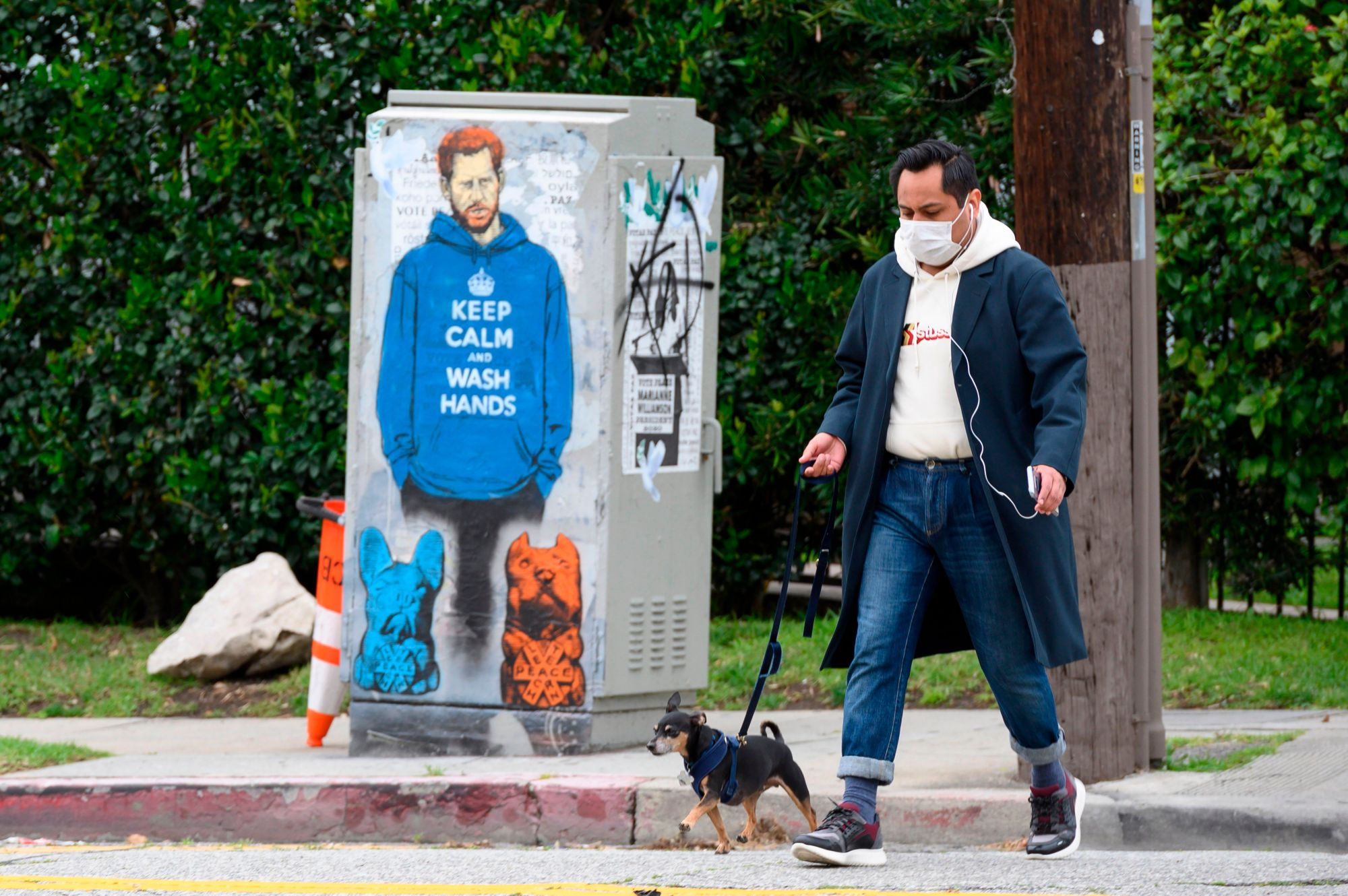 "People walk past a painting of Prince Harry wearing a hoodie reading ""Keep Calm and Wash Your Hands,"" on April 7, 2020, during the coronavirus pandemic in Los Angeles. (ROBYN BECK/AFP via Getty Images)"
