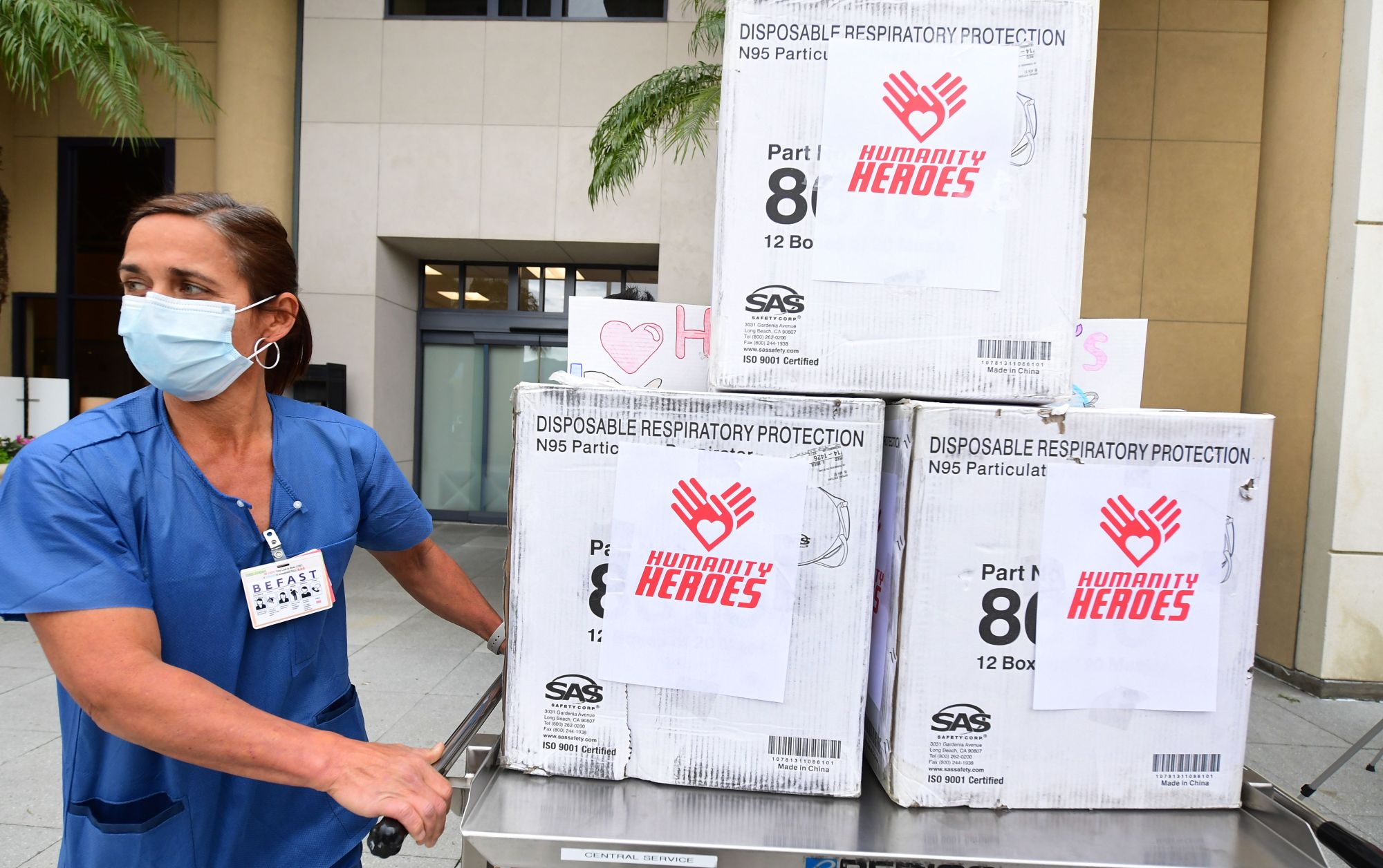 A nurse wearing a facemask pushes a cart of masks to Providence Saint Joseph Medical Center in Burbank on April 7, 2020, during the novel coronavirus outbreak. (FREDERIC J. BROWN/AFP via Getty Images)