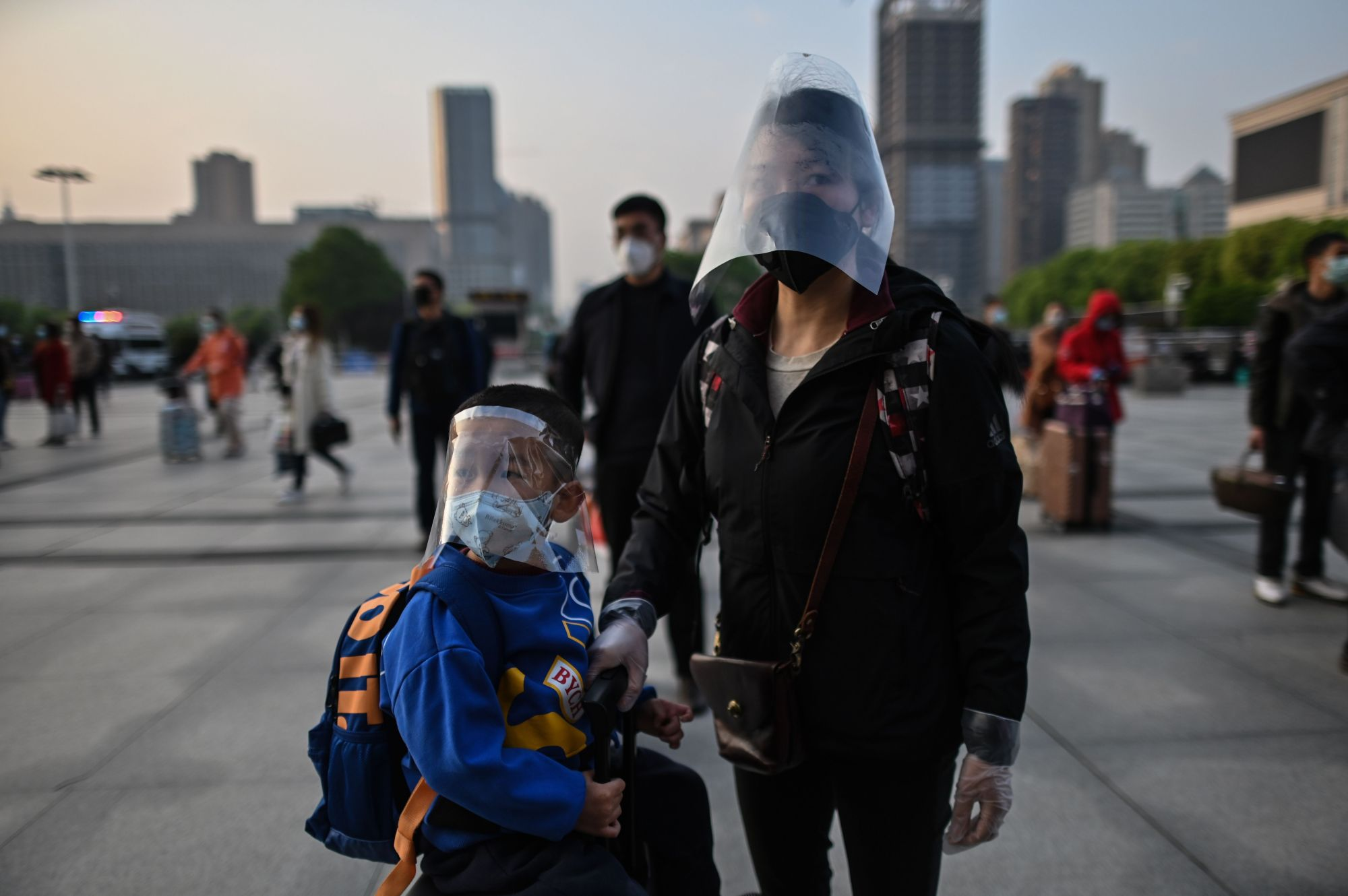 A boy wearing a face shield on top of a face mask waits with his mother to board one of the first trains leaving Wuhan after an outbound travel ban was lifted, at the Hankou railway station in Wuhan in China's central Hubei province early on April 8, 2020. (HECTOR RETAMAL/AFP via Getty Images)