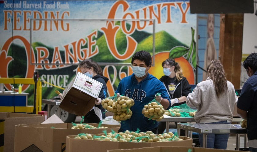 Jose Secundino, center, joins other recently hired temporary employees at Second Harvest Food Bank of Orange County to pack boxes of food for the needy on April 1, 2020. (Credit: Allen J. Schaben / Los Angeles Times)