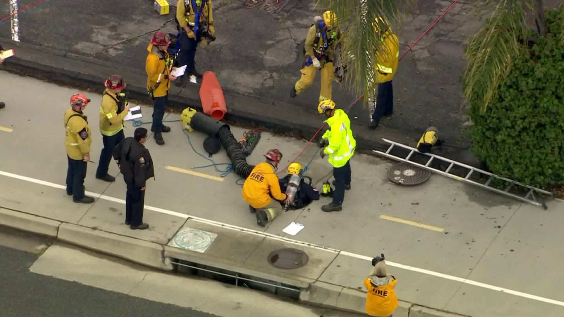 A rescuer goes inside the storm drain were a person is trapped near a Lakewood-area golf course on April 6, 2020. (KTLA)